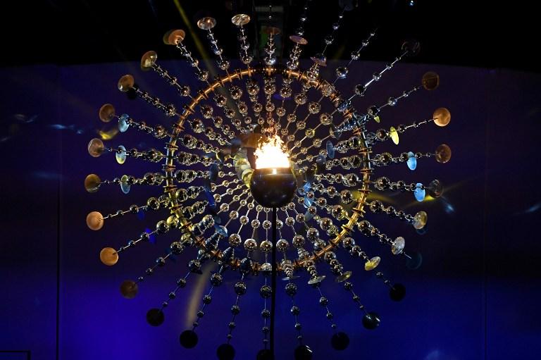 Estrutura metálica que forma um Sol, refletindo o brilho da chama (Foto: WilliamI West/AFP)